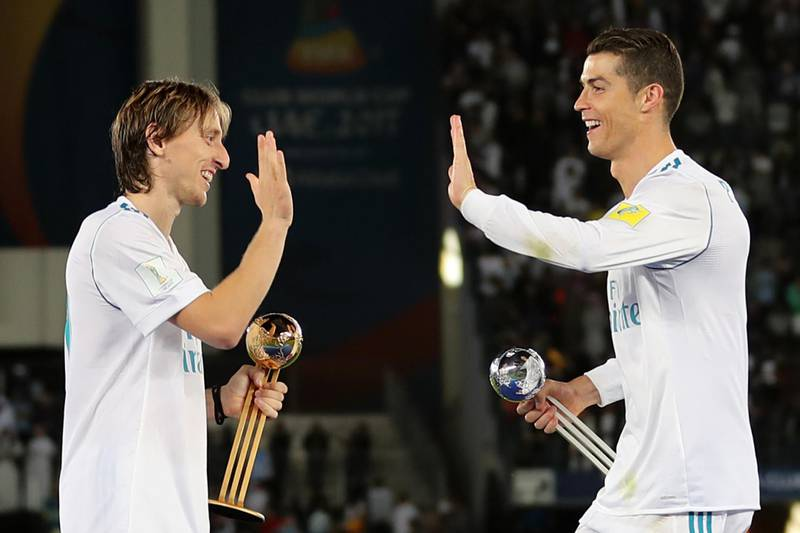 Real Madrid's Portuguese forward Cristiano Ronaldo (R) holding his 2017 FIFA Club World Cup Silver Ball award celebrates with his teammate Luka Modric holding his 2017 FIFA Club World Cup gold award after winning the FIFA Club World Cup final football match against Gremio FBPA at the Zayed Sports City Stadium in Abu Dhabi on December 16, 2017. Real Madrid defeated Gremio 1-0 to lift the FIFA Club World Cup for the third time. / AFP PHOTO / KARIM SAHIB