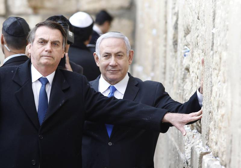 TOPSHOT - Brazilian President Jair Bolsonaro (L) and Israeli Prime Minister Benjamin Netanyahu touch the Western wall, the holiest site where Jews can pray, in the Old City of  Jerusalem on April 1, 2019. Bolsonaro arrived in Israel just ahead of the country's polls in which his ally Prime Minister Benjamin Netanyahu faces a tough re-election fight. / AFP / POOL / Menahem KAHANA