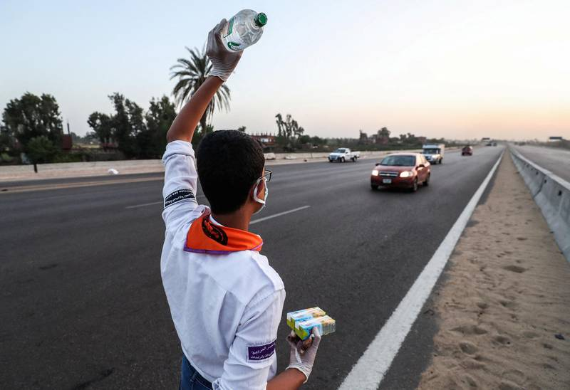 A boyscout volunteering to distribute water, food and juice, signals to fasting drivers on a road in Egypt's Menoufia governorate on April 27, 2020, during the Muslim holy month of Ramadan. (Photo by Mohamed el-Shahed / AFP)
