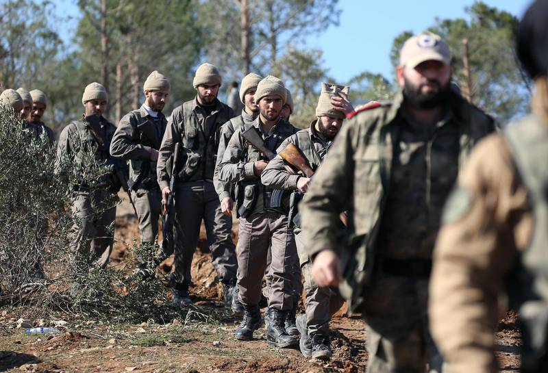 """Turkish-backed Syrian rebels march on Mount Barsaya north of Azaz, on January 29, 2018, as the Turkish offensive against Kurdish forces in the Syrian border region of Afrin continues. Turkey launched operation """"Olive Branch"""" on January 20 against the Syrian Kurdish People's Protection Units (YPG) militia in Afrin, supporting Syrian opposition fighters with ground troops and air strikes. / AFP PHOTO / Nazeer al-Khatib"""