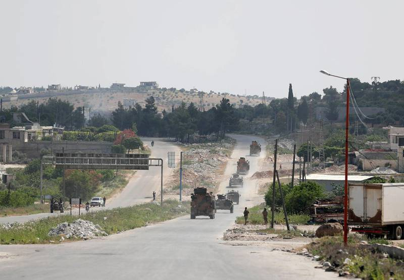 Military vehicles of a joint Russian-Turkish patrol pass through the M4 highway on the outskirts of the rebel-held town of Ariha in Syria's northwestern Idlib province on May 7, 2020.  / AFP / Omar HAJ KADOUR