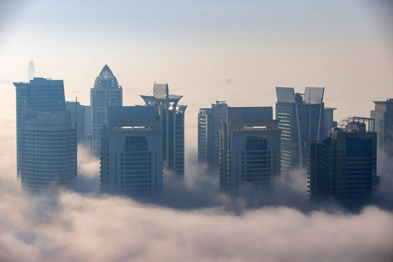Morning fog shrouds residential and commercial skyscrapers in the Jumeirah Lakes Towers district of Dubai, United Arab Emirates, on Sunday, Jan. 17, 2021. Dubai is hoping one of the world's fastest vaccination programs and rapid testing technology will help achieve its goal of holding the Expo 2020 event this year, after the coronavirus pandemic forced a delay. Photographer: Christopher Pike/Bloomberg