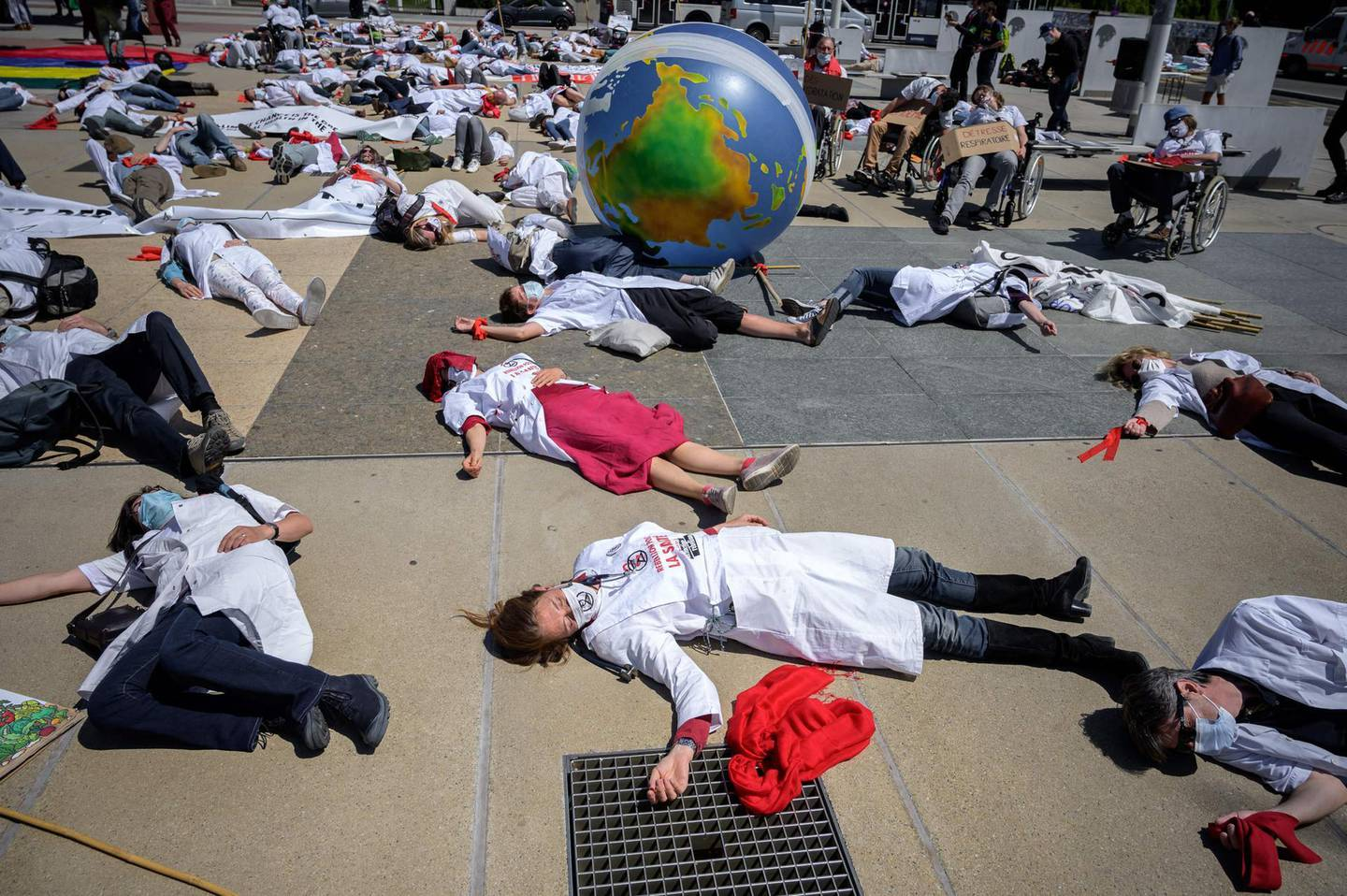 Doctors for Extinction Rebellion lay down prior to march to the WHO headquarters during a protest on the sideline of the WHO's World Health Assembly in Geneva on May 29, 2021. Hundreds of health workers marched to the WHO demanding that authorities in all countries recognise and act to counter the health risks of climate change. / AFP / Fabrice COFFRINI