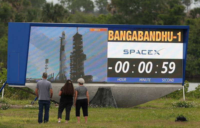 People are gathered in front of the countdown clock as the SpaceX Falcon 9 rocket launch was scrubbed Thursday, May 10, 2018, from launch Pad39A at the Kennedy Space Center, in Fla. This latest version of the Falcon 9 was supposed to blast off Thursday, carrying Bangladesh's first satellite, which would bring the internet to all corners of the country. (Red Huber/Orlando Sentinel via AP)