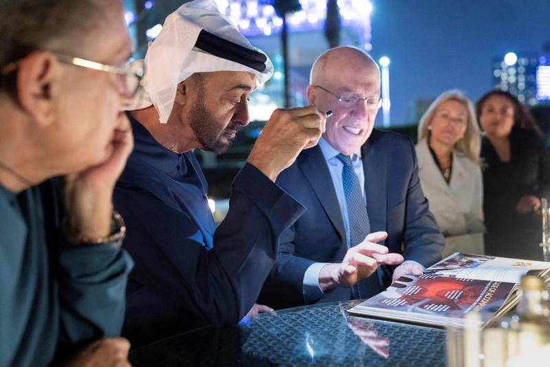 AL MARYAH ISLAND, ABU DHABI, UNITED ARAB EMIRATES - December 13, 2019: HH Sheikh Mohamed bin Zayed Al Nahyan, Crown Prince of Abu Dhabi and Deputy Supreme Commander of the UAE Armed Forces (2nd L), looks at a book with Dr Kurt Newman, President and CEO of Children's National Medical Center (3rd L), during a meeting at the Rosewood Hotel.  ( Ryan Carter / Ministry of Presidential Affairs ) ---