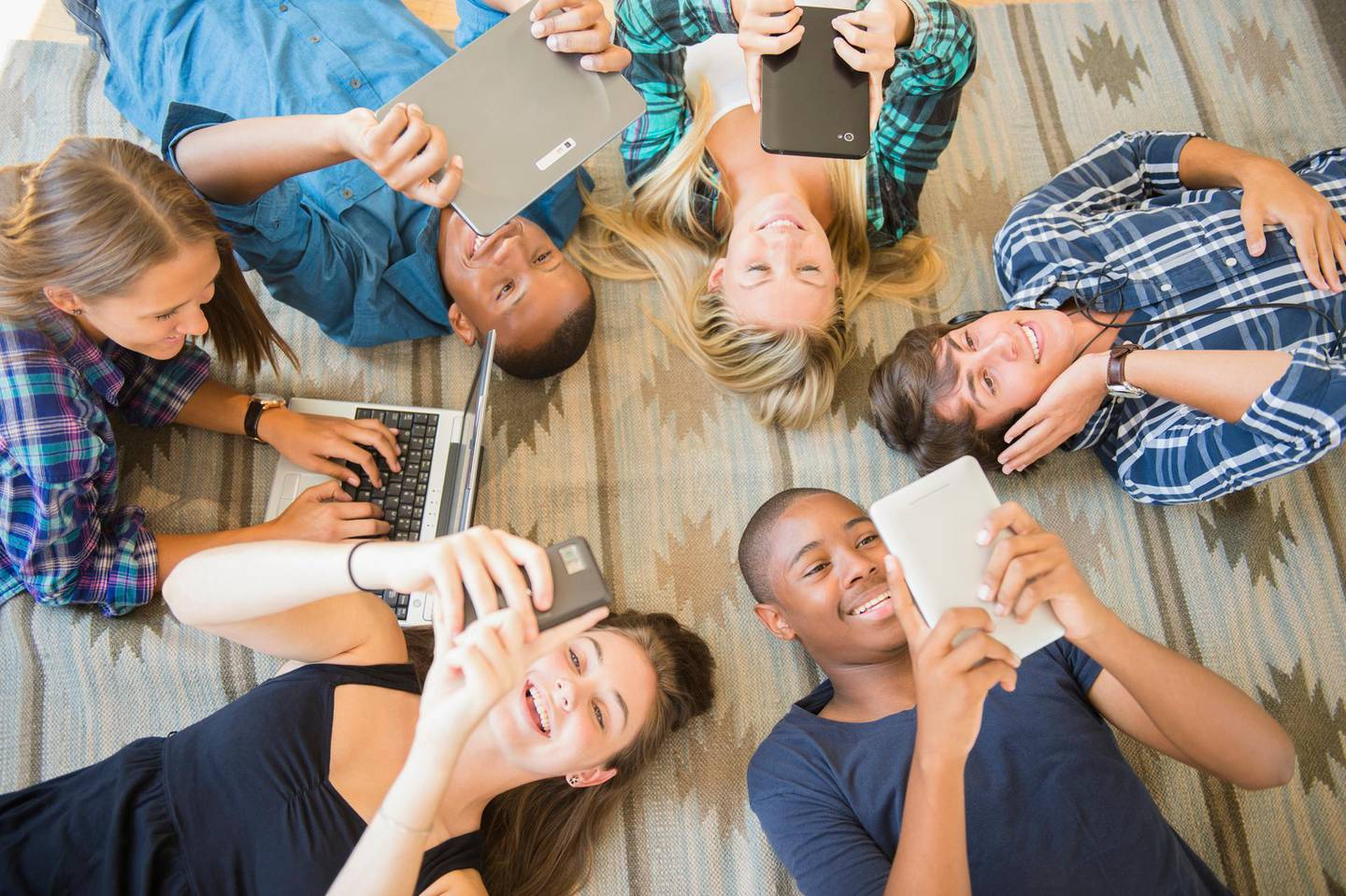 Teenagers laying on floor using technology. Getty Images