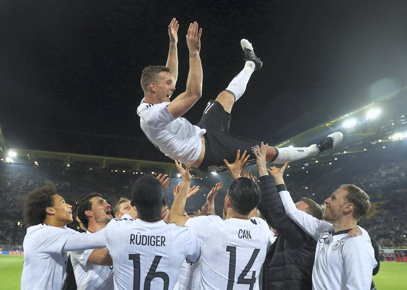DORTMUND, GERMANY - MARCH 22:  Lukas Podolski is thrown in the air by his team mates after playing his last game for Germany during the international friendly match between Germany and England at Signal Iduna Park on March 22, 2017 in Dortmund, Germany.  (Photo by Alex Grimm/Bongarts/Getty Images)