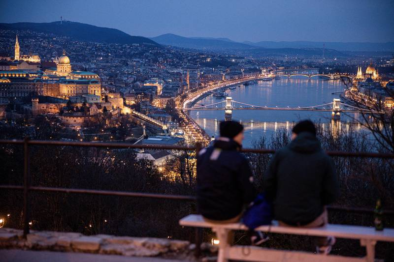 Visitors look out over the city skyline and the Chain Bridge at night in Budapest, Hungary, on Tuesday, March 9, 2021. Prime MinisterViktor Orbanseverely tightened curbs, closing schools and nearly all retail outlets from Monday. Photographer: Akos Stiller/Bloomberg