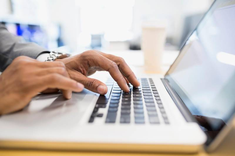 Close up businessman typing on laptop. Getty Images