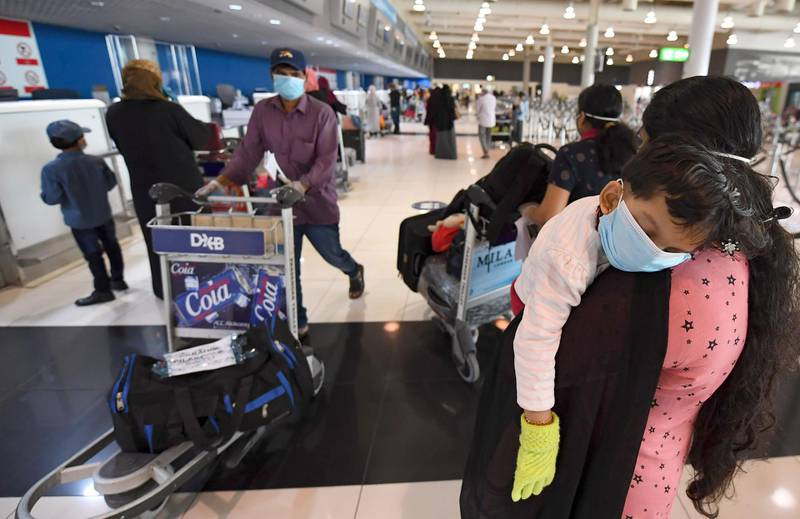An Indian woman carries a sleeping child as she waits at the Dubai International Airport before leaving the Gulf Emirate on a flight back to her country, on May 7, 2020, amid the novel coronavirus pandemic crisis.  The first wave of a massive exercise to bring home hundreds of thousands of Indians stuck abroad was under way today, with two flights preparing to leave from the United Arab Emirates. India banned all incoming international flights in late March as it imposed one of the world's strictest virus lockdowns, leaving vast numbers of workers and students stranded.           / AFP / Karim SAHIB