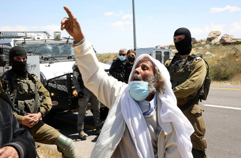 epa09124319 A Palestinian protester argues with Israeli security forces as he protests against Israeli settlement building activities on their land in the village of West Bank Yatta, near Hebron, 09 April 2021.  EPA/ABED AL HASHLAMOUN