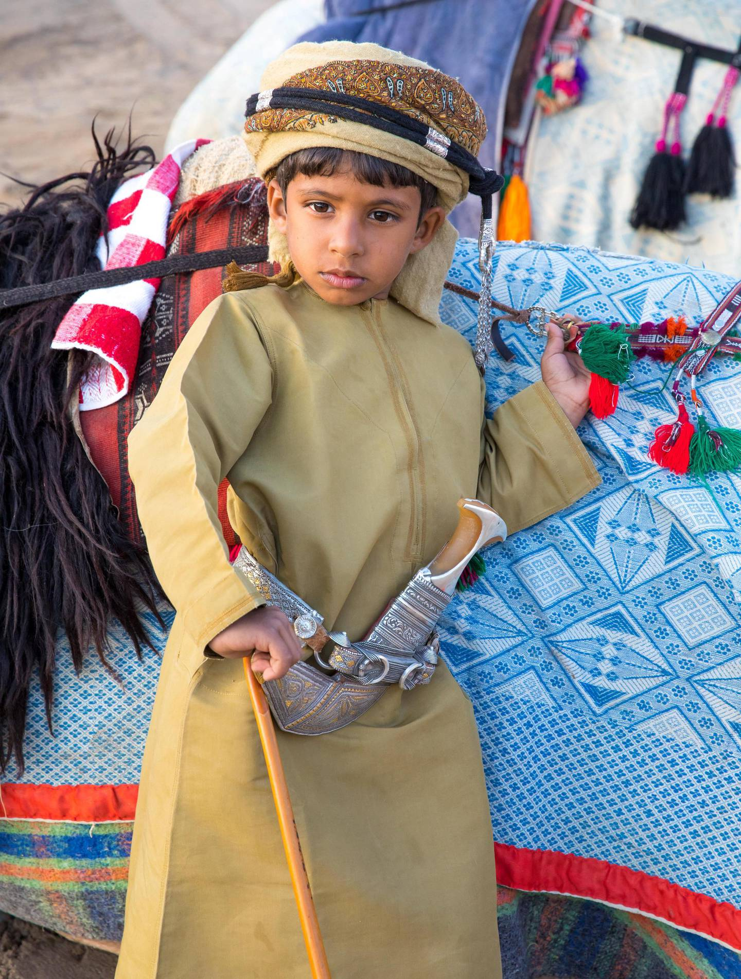 HR57YJ Muscat, Oman - Feb 4, 2017: Young Omani boy dressed in traditional clothing posing next to his camel.