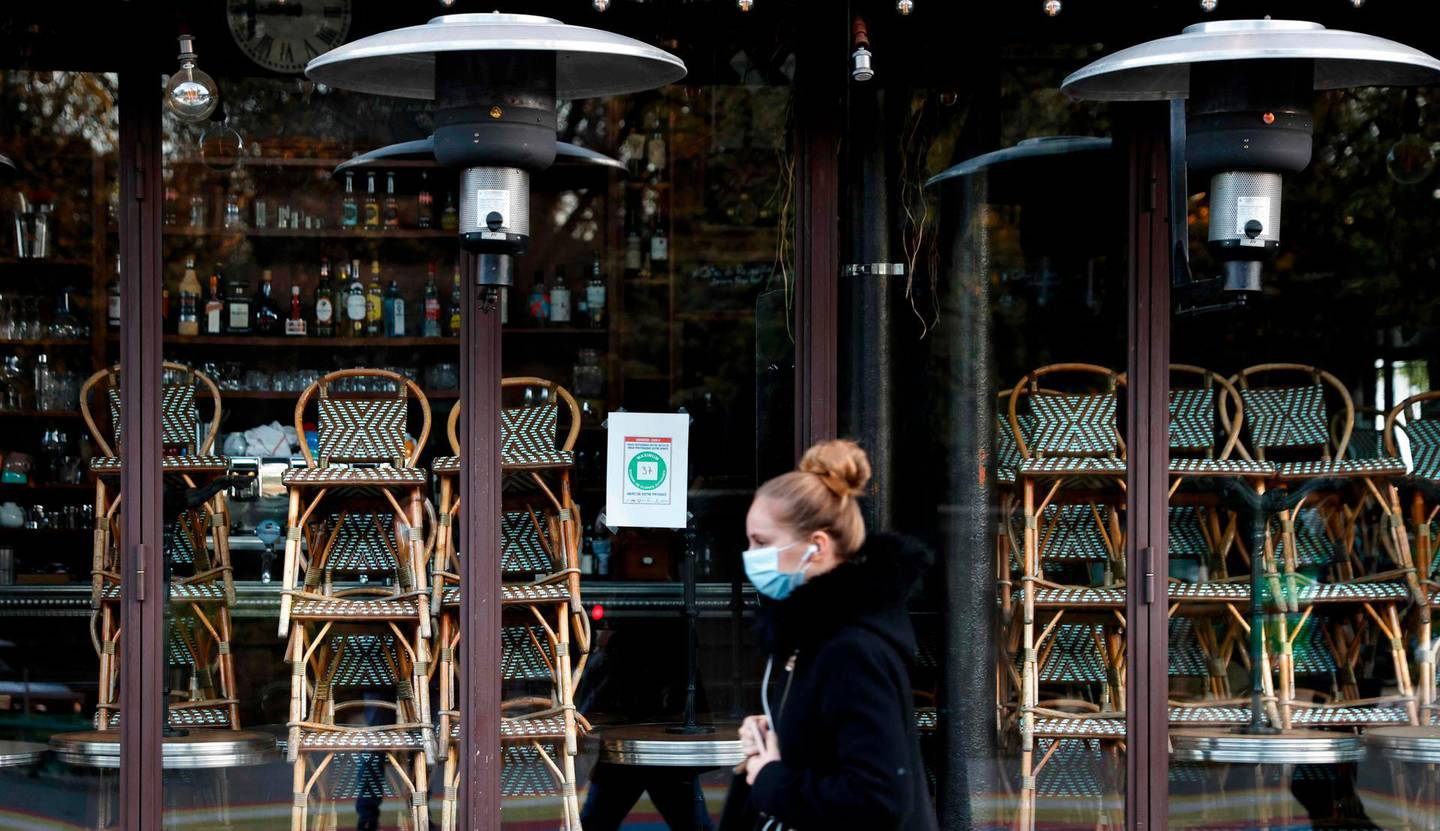 A woman walks past a closed restaurant in Paris on November 18, 2020, amid a second lockdown in France aimed at containing the spread of Covid-19 pandemic caused by the novel coronavirus. / AFP / THOMAS COEX