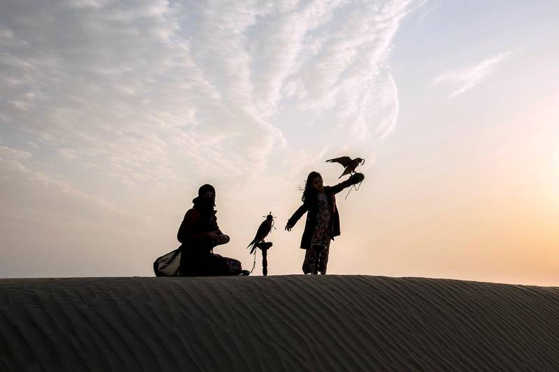 After the training session Ayesha and Osha , stand with their falcon at twilight , Abu Dhabi ,UAE , Vidhyaa Chandramohan for The National