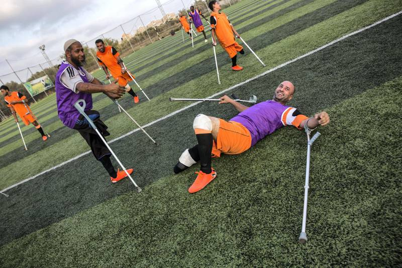 """Wahid Rabah, the oldest member of Gaza's new amputee football team , smiles despite falling to the ground during  the team's weekly practise session on July 16,2018. He lost his right leg during an Israeli military operation in 2006 called """"Summer Rain,"""" which was launched after an Israeli soldier was captured and taken into Gaza. (Photo by Heidi Levine for The National)."""