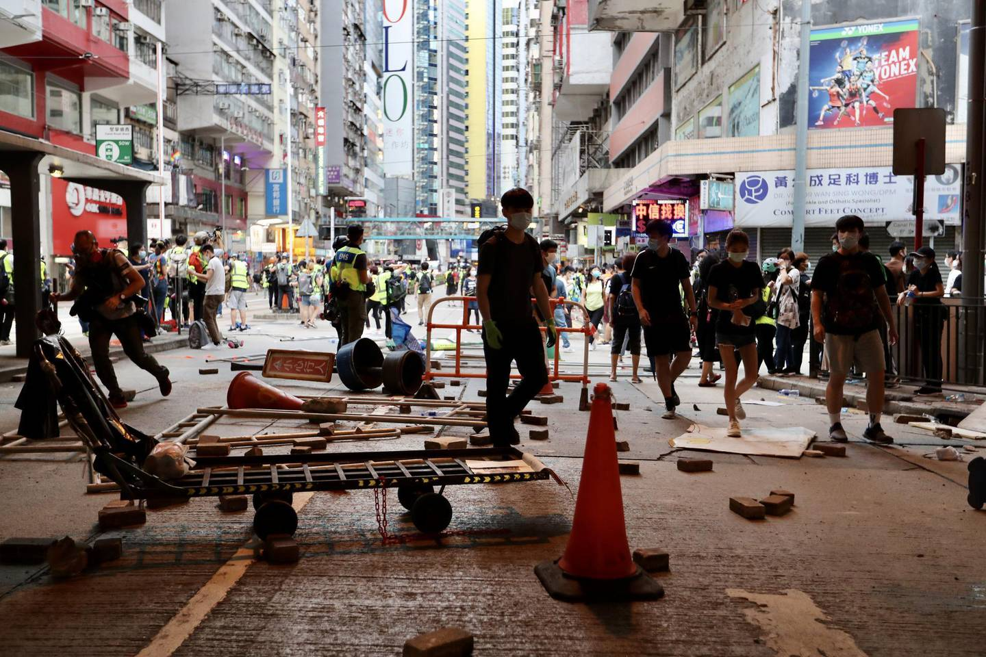 People move around the debris of roadblocks set by protesters during a protest against a planned national security law in the Wan Chai district in Hong Kong, China, on Sunday, May 24, 2020. Almost 200 politicians and legislators from 23 countries issued a joint statement criticizing China's plans to impose a sweeping national security law in Hong Kong, and warned that it could spark more protests in the city, Radio and Television Hong Kongreported. Photographer: May James/Bloomberg