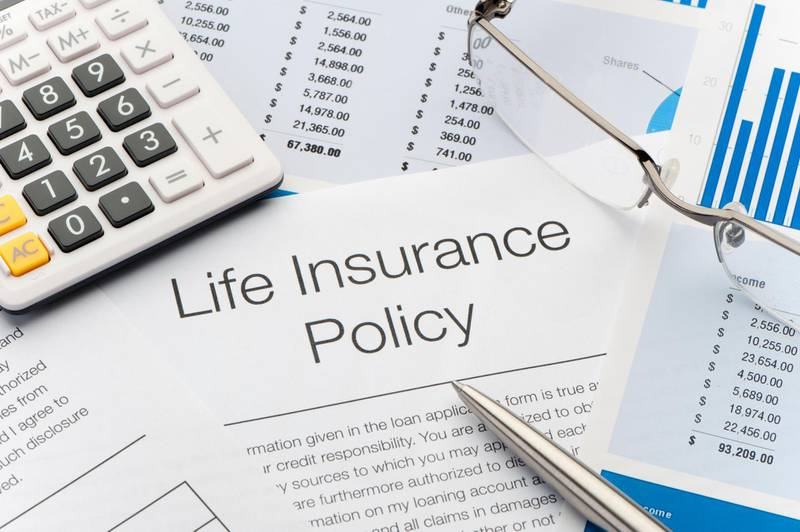 Close up of Life Insurance Policy with pen, calculator