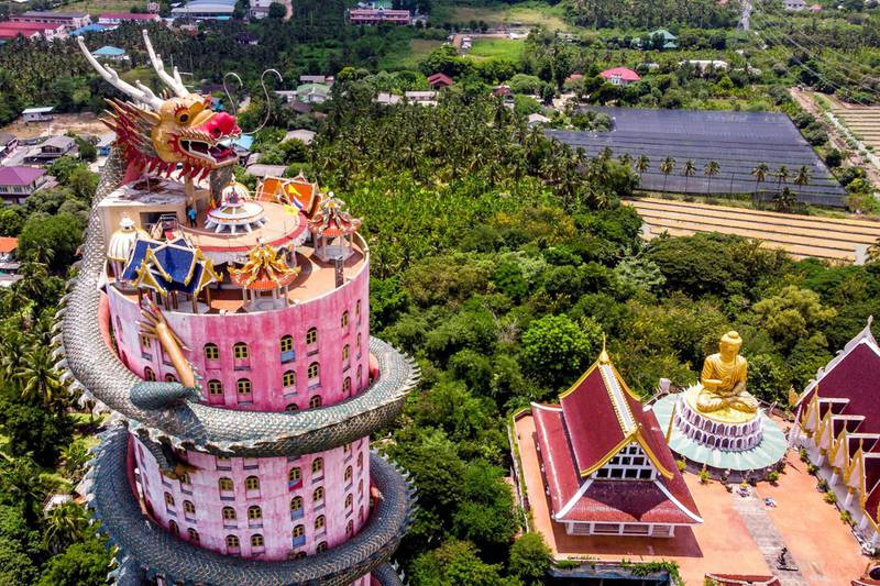 An aerial view taken on September 11, 2020 shows the Buddhist temple Wat Samphran (Dragon Temple) in Nakhon Pathom, some 40km west of Bangkok. Wat Samphran is a popular tourist destination with visitors coming to see the huge dragon figure curling around a pink cylindrical building next to the Buddha statues and places of worship of the traditional Buddhist temple complex. / AFP / Mladen ANTONOV