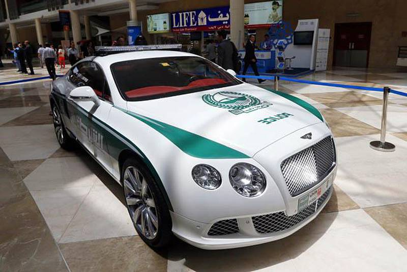 """People walk past the new Dubai police Bentley patrol car on display during the Arabian Travel Market (ATM) at the Dubai World Trade Centre in the Emirati city on May 6, 2013. Dubai police have introduced top end sports cars to their patrol fleet to further strengthen the image of """"luxury and prosperity"""" of the Emirate. AFP PHOTO/KARIM SAHIB"""