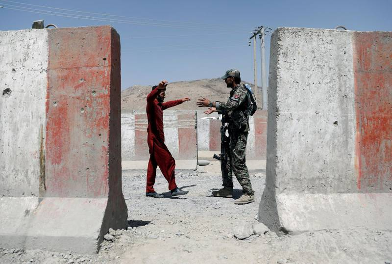An Afghan National Army (ANA) soldier inspects a passenger at a checkpoint on the Ghazni - Kabul highway, Afghanistan August 14, 2018.REUTERS/Mohammad Ismail      TPX IMAGES OF THE DAY