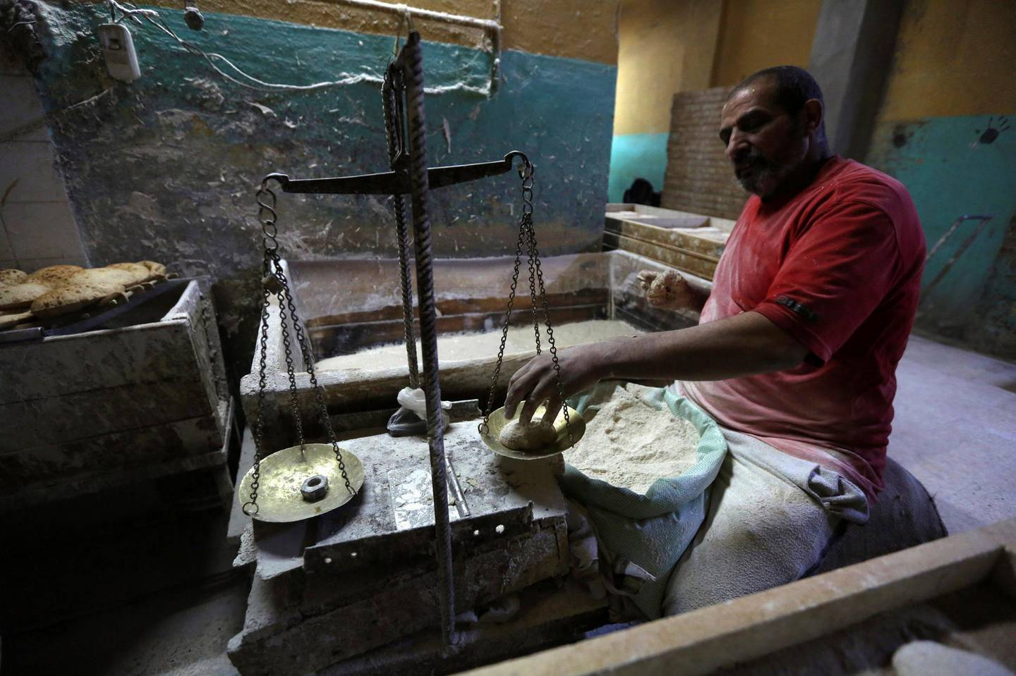 FILE PHOTO: A worker weighs dough to be baked into bread at a bakery in Cairo, January 8, 2015. REUTERS /Mohamed Abd El Ghany/File Photo