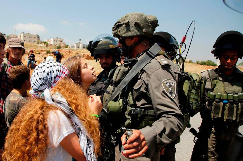 (FILES) This file photo taken on May 12, 2017 shows 17-year-old Ahed Tamimi (C) protesting before Israeli forces in the West Bank village of Nabi Saleh, north of Ramallah, on May 12, 2017, after a demonstration following Friday prayers in solidarity with Palestinian prisoners on hunger strike in Israeli jails. Israel's army arrested Ahed Tamimi on December 19, 2017, after a video went viral of her slapping Israeli soldiers in the occupied West Bank as they remained impassive. / AFP PHOTO / ABBAS MOMANI