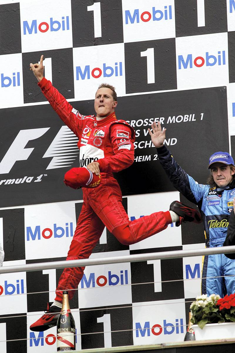 Michael Schumacher, Fernando Alonso, Grand Prix of Germany, Hockenheimring, 25 July 2004. Michael Schumacher performing one of his famous victory jumps on the podim of the 2004 Grand Prix of Germany. (Photo by Paul-Henri Cahier/Getty Images)