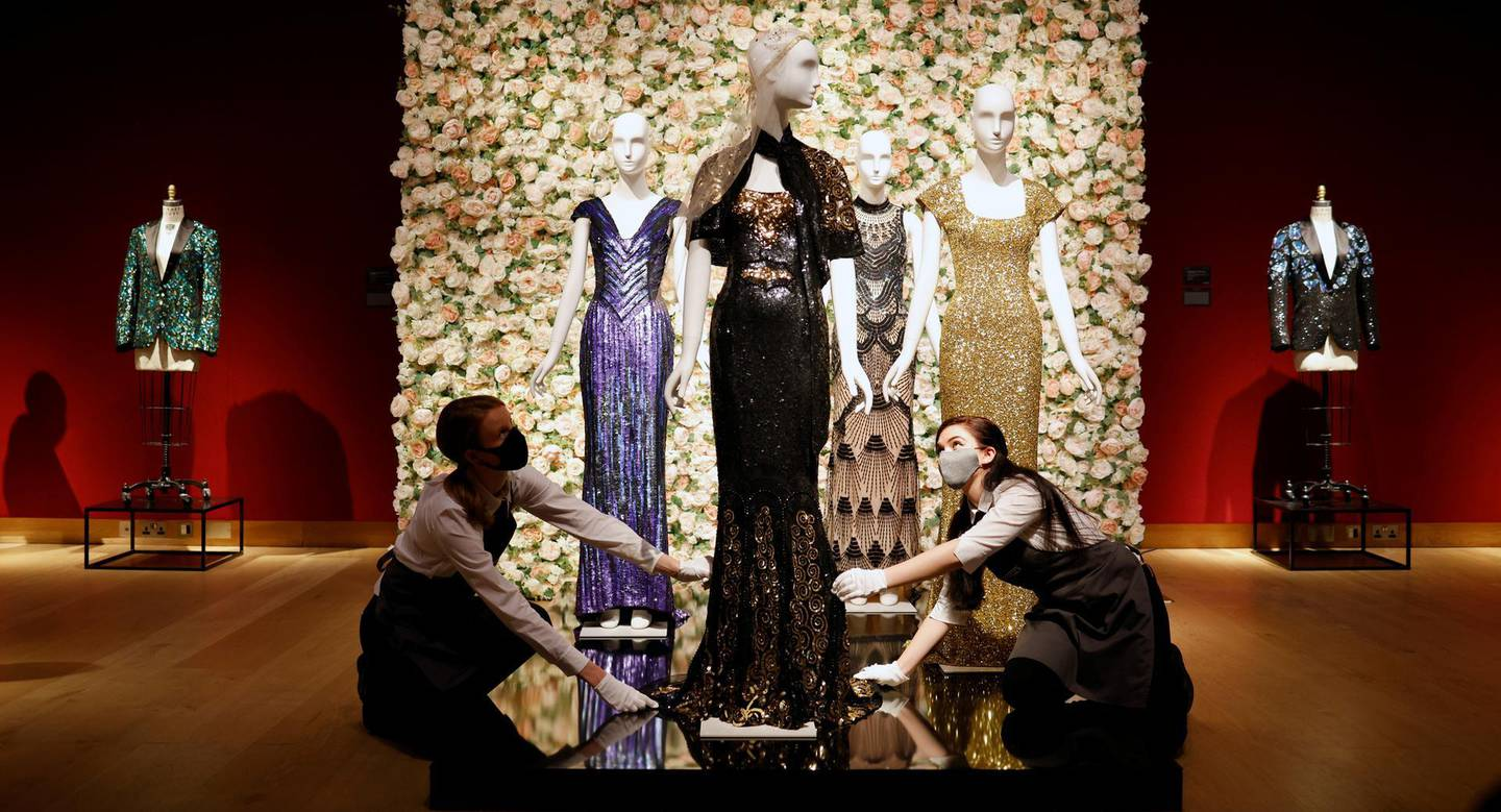 Gallery assistants pose for a photograph next to a black and gold 'Oscar' dress worn by Nicole Kidman by designer L'Wren Scott at Christie's in London, Britain, June 10, 2021. REUTERS/John Sibley