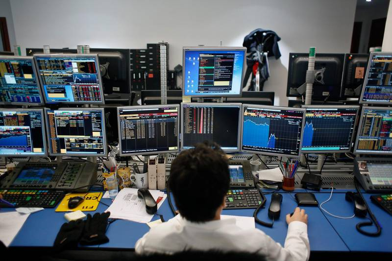 A currency trader watches monitors in a brokerage firm in Paris, France, Tuesday, Feb. 6, 2018. Stock markets around the world took a battering Tuesday, following a dramatic sell-off on Wall Street that triggered concerns that a potentially healthy pullback from record highs could turn into a protracted bear market. (AP Photo/Thibault Camus)