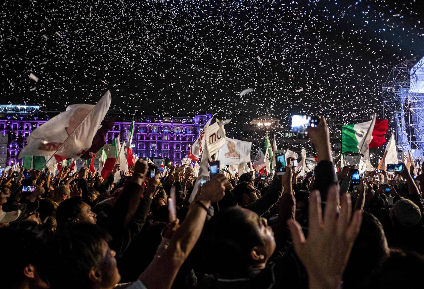 """Supporters of the presidential candidate for the """"Juntos haremos historia"""" coalition, Andres Manuel Lopez Obrador, celebrate at the Zocalo square in Mexico City, after getting the preliminary results of the general elections on July 1, 2018.  Anti-establishment leftist Andres Manuel Lopez Obrador won Mexico's presidential election Sunday by a large margin, according to exit polls, in a landmark break with the parties that have governed for nearly a century. / AFP / Guillermo Arias"""