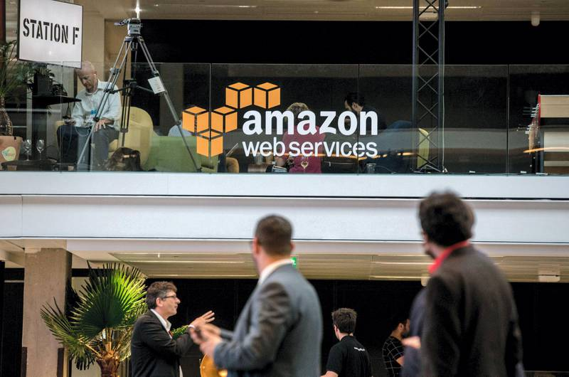 Attendees stand near Amazon.com Inc. Web Services signage during the Station F startup campus launch party in Paris, France, on Thursday, June 29, 2017. One of France's richest people, Niel spent 250 million euros ($268 million) to transform a former freight station into an incubator area, with some 3,000 desks for rent and numerous hangout areas. Photographer: Christophe Morin/Bloomberg