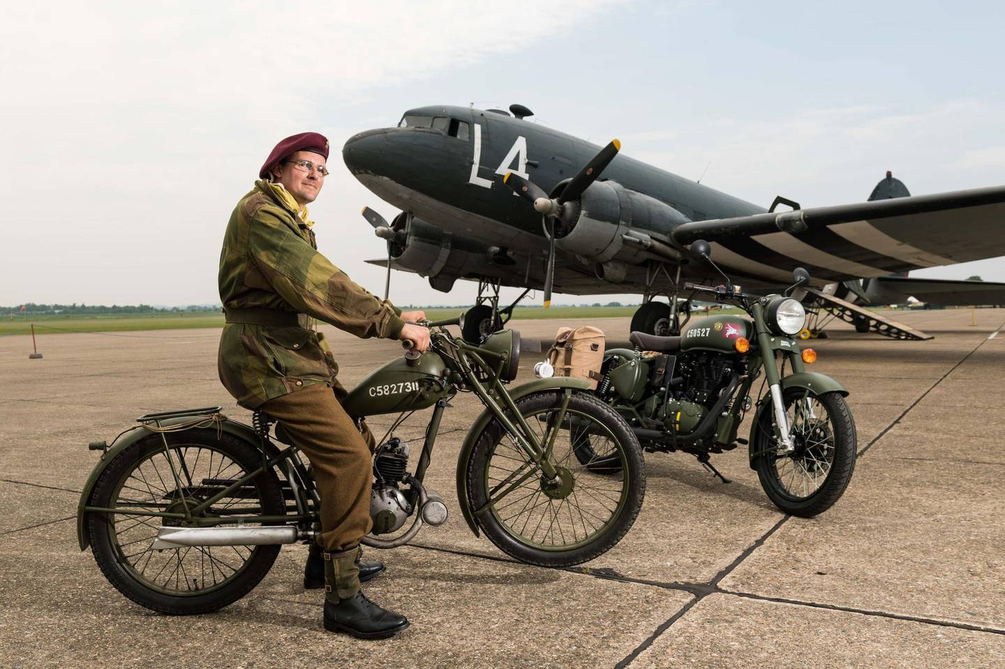 DUXFORD, ENGLAND - May 21:  A member of the Living History reenactment group poses with both the original Royal Enfield Flying Flea motorcycle and the 'Classic 500 Pegasus' motorcycle at IWM Duxford on May 21, 2018 in Duxford, England.  A new limited edition Royal Enfield 'Classic 500 Pegasus' motorcycle pays tribute to the original Royal Enfield Flying Flea, the legendary lightweight World War Two British paratroopers' motorcycle.  (Photo by Ian Gavan/Getty Images for Royal Enfield)