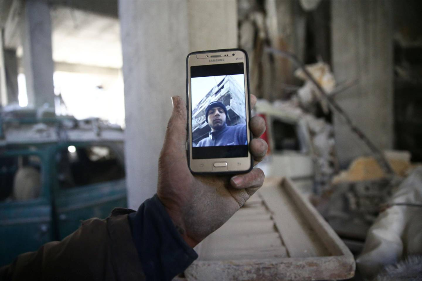 Abu Mohammad Alaya, 50, holds a mobile phone with his son Mohammad's picture on the screen, who was killed, in Douma, Syria March 2, 2018. Picture taken March 2, 2018. REUTERS/Bassam Khabieh
