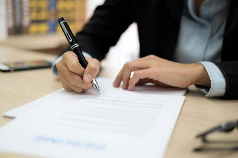 Close up of woman signing contract in job application form. Getty Images