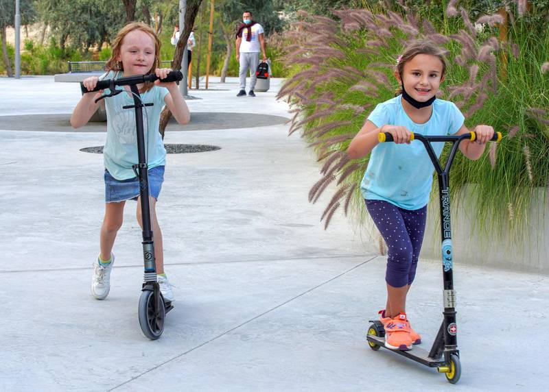 Abu Dhabi, United Arab Emirates, January 21, 2021. (L-R)   Tala, 7 and Amelia, 8 scooter around Al Fay Park on Reem Island.Victor Besa/The National Section:  LFReporter: Panna Munyal