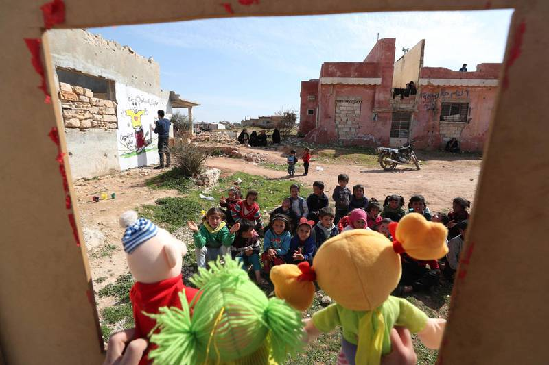 Syrian children watch a puppet show performed by a local theatre group amidst the ruins of buildings destroyed during Syria's civil war, in al-Fua, in the country's northwestern Idlib province on March 30, 2021.  / AFP / OMAR HAJ KADOUR