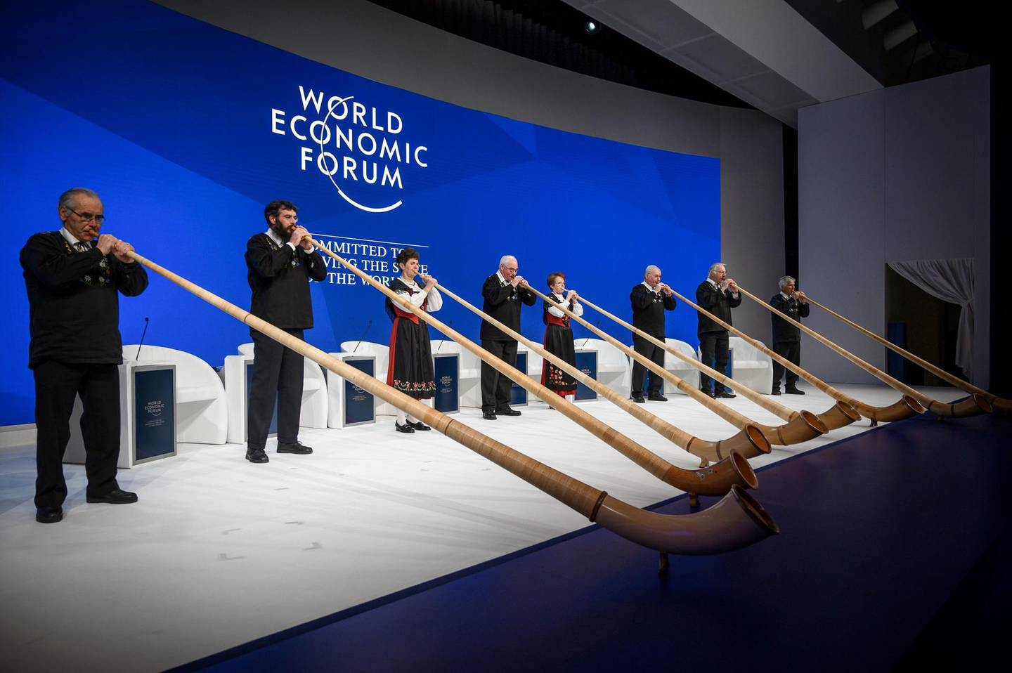 Alphorn blowers perform during the opening of the World Economic Forum (WEF) annual meeting, on January 22, 2019 in Davos, eastern Switzerland.  / AFP / Fabrice COFFRINI