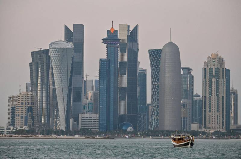 A general view taken on December 20, 2019 shows boats moored in front of the skyline of the Qatari capital, Doha. (Photo by GIUSEPPE CACACE / AFP)