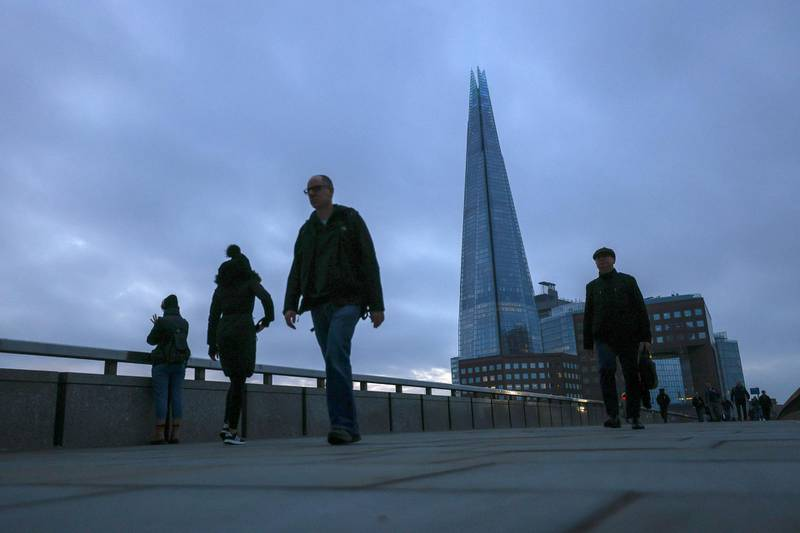 FILE PHOTO: Pedestrians walk on London Bridge with the Shard in the background, in London, Britain November 25, 2020. REUTERS/Simon Dawson/File Photo