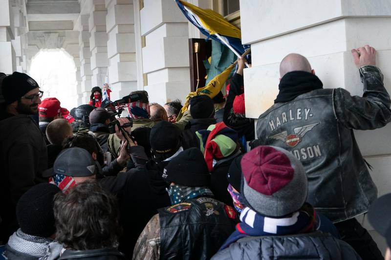 FILE - In this Jan. 6, 2021 file photo insurrectionists loyal to President Donald Trump try to open a door of the U.S. Capitol as they riot in Washington. At least a dozen of the 400 people charged so far in the Jan. 6 insurrection have made dubious claims about their encounters with officers at the Capitol. The most frequent argument is that they can't be guilty of anything, because police stood by and welcomed them inside, even though the mob pushed past police barriers, sprayed chemical irritants and smashed windows as chaos enveloped the government complex.  (AP Photo/Jose Luis Magana, File)