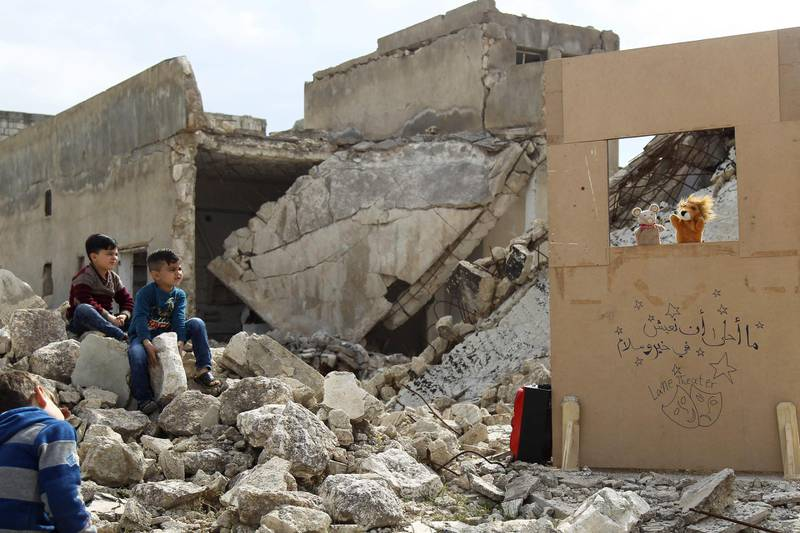 (FILES) In this file photo taken on March 27, 2019, children watch a puppet show performed by a Syrian actor, through a makeshift puppet theatre set up among the rubble of collapsed buildings in the town of Saraqib in the rebel-held northern Idlib province.  / AFP / Amer ALHAMWE