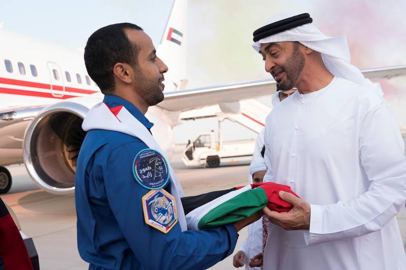 ABU DHABI, UNITED ARAB EMIRATES - October 12, 2019: HH Sheikh Mohamed bin Zayed Al Nahyan, Crown Prince of Abu Dhabi and Deputy Supreme Commander of the UAE Armed Forces (R), receives the UAE flag which travelled to the International Space Station (ISS) mission with the Hazza Ali Al Mansoori (L), the first UAE Astronaut to be deployed on a space mission, during a homecoming reception at the Presidential Airport.    ( Mohamed Al Hammadi / Ministry of Presidential Affairs ) ---
