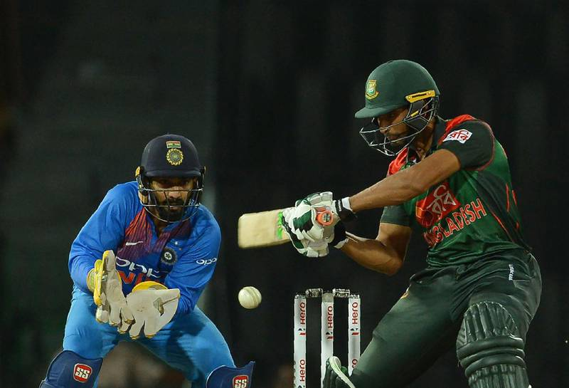 Bangladesh cricket captain Mahmudullah (R) is watched by Indian wicketkeeper Dinesh Karthik as he plays a shot during the fifth Twenty20 (T20) international cricket match between India and Bangladesh of the tri-nation Nidahas Trophy at the R. Premadasa stadium in Colombo on March 14, 2018. / AFP PHOTO / LAKRUWAN WANNIARACHCHI