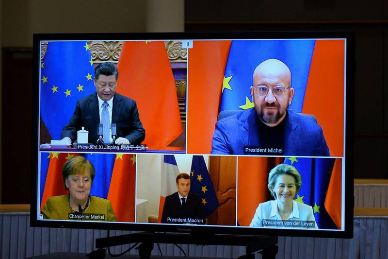 European Commission President Ursula von der Leyen, European Council President Charles Michel, German Chancellor Angela Merkel, French President Emmanuel Macron and Chinese President Xi Jinping are seen on a screen during a video conference, in Brussels, Belgium December 30, 2020. REUTERS/Johanna Geron/Pool
