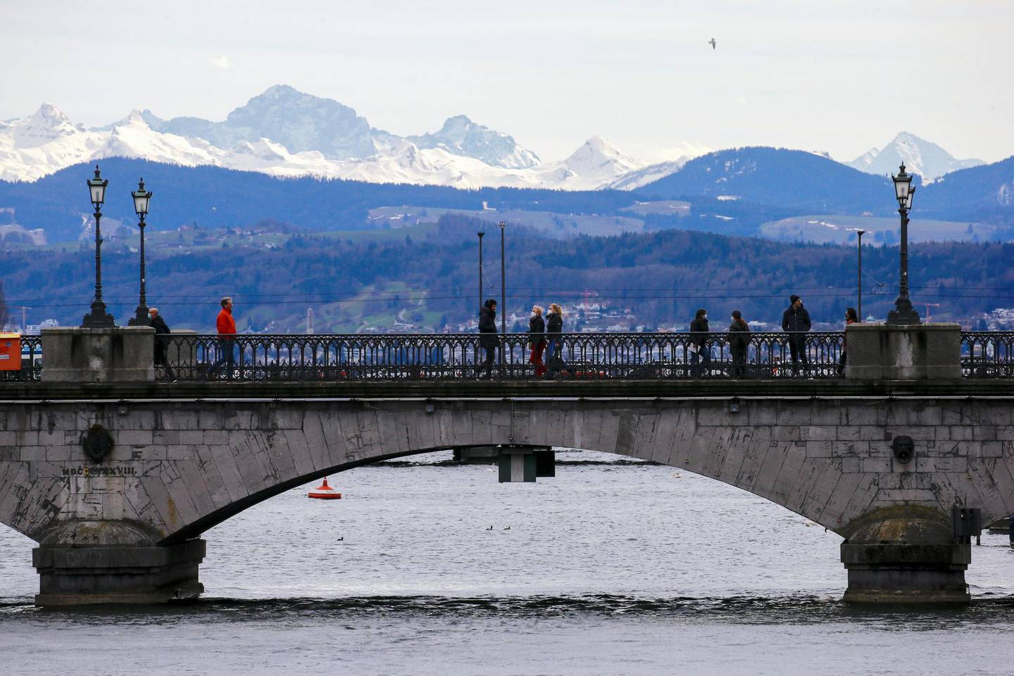 Eastern Swiss Alps are seen in the background as people cross the Limmat River on the Muensterbruecke bridge, as the spread of the coronavirus disease (COVID-19) continues, in Zurich, Switzerland March 13, 2021. REUTERS/Arnd Wiegmann