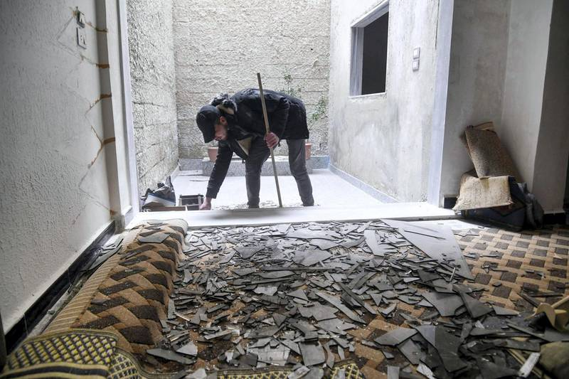 """A handout picture released by the official Syrian Arab News Agency (SANA) on April 27, 2020 shows a man cleaning debris at his home after an Israeli air strike, south of the Syrian capital Damascus. - Israeli air strikes near the Syrian capital early Monday killed three civilians, state media said. """"Three civilians were martyred and four others wounded, including a child, because shrapnel from Israeli missiles fell on houses"""" in the suburbs of Damascus, the official SANA news agency said. Syrian air defences had downed """"most"""" of the Israeli missiles launched from Lebanese air space shortly before dawn, SANA said in an earlier report. (Photo by - / various sources / AFP) / == RESTRICTED TO EDITORIAL USE - MANDATORY CREDIT """"AFP PHOTO / HO / SANA"""" - NO MARKETING NO ADVERTISING CAMPAIGNS - DISTRIBUTED AS A SERVICE TO CLIENTS =="""