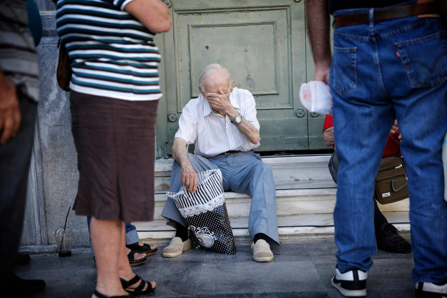 Pensioners wait to enter a National Bank of Greece SA bank branch to collect their pension payments in Athens, Greece, on Friday, July 17, 2015. Germany's Parliament is set to ratify bridge financing and the start of talks for a three-year rescue plan. Photographer: Matthew Lloyd/Bloomberg