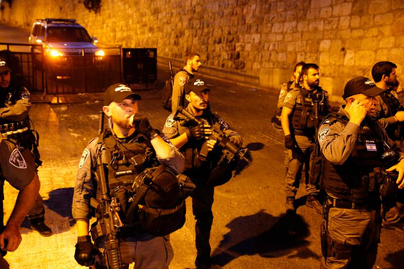 Israeli border guards stand at attention as Palestinian Muslim worshippers pray outside Lions' Gate, a main entrance to the Al-Aqsa mosque compound in Jerusalem's Old City, on July 22, 2017, in protest against new Israeli security measures implemented at the holy site following an attack that killed two Israeli policemen the previous week. Stabbings and clashes that left six people dead raised fears of further Israeli-Palestinian violence as tensions mount over new security measures at the highly sensitive Jerusalem holy site. / AFP PHOTO / AHMAD GHARABLI