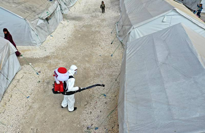 A drone image taken on April 9, 2020, shows a sanitation worker disinfecting a camp for displaced Syrians next to the Idlib municipal stadium in the northwestern Syrian city, during a campaign to limit the spread of the coronavirus (COVID-19) pandemic. (Photo by OMAR HAJ KADOUR / AFP)
