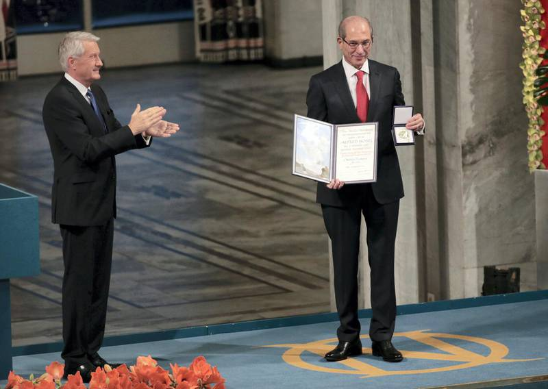 The Chairman of the Norwegian Nobel Committee Thorbjoern Jagland (L) applauds after awarding Ahmet Uzumcu (R), Director General of the Organisation for the Prohibiton of Chemical Weapons (OPCW), the 2013 Peace Nobel Prize at the Oslo City Hall on December 10, 2013. The Organisation for the Prohibiton of Chemical Weapons (OPCW) received the 2013 Peace Nobel Prize, attributed for its extensive efforts to eliminate chemical weapons.   AFP PHOTO / DANIEL SANNUM LAUTEN / AFP PHOTO / DANIEL SANNUM LAUTEN